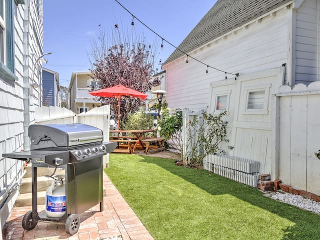 The private backyard features a grill and decorative string lights.