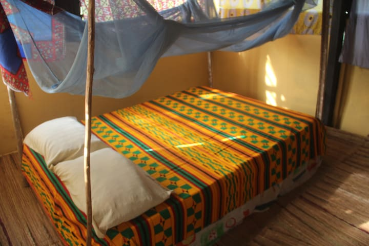 Double bed in top room of treehouse with mozzie net