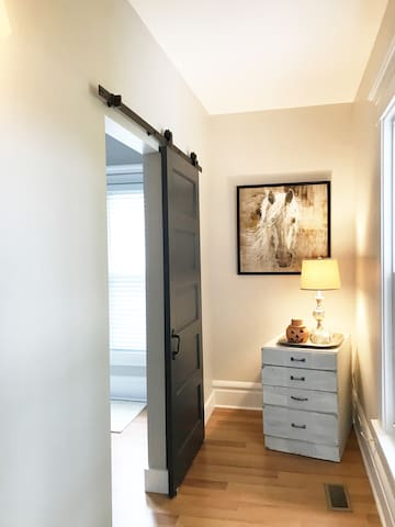 Love solid Barn doors offering privacy for the Queen bedroom! This reclaimed cabinet houses a hairdryer, extra toilet paper, and some overnight essentials if left at home.  Notice the seasonal decorations that we offer our guests. #1 Retreat