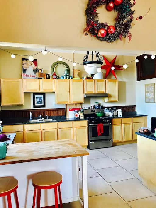 The kitchen is fully stocked with pots, pans, plates, and glassware, along with cooking basics such as spices, salt, oil, etc.