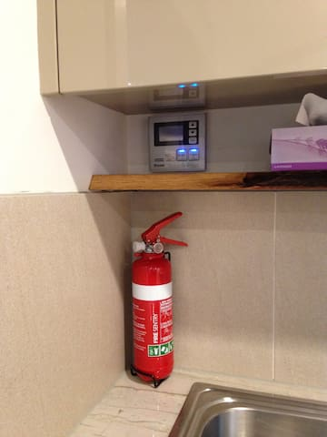 Fire extinguisher and on/off for the hot water service, above the sink.