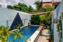 """Balcony peeking through the trees, overlooking the pool. """"Their house is absolutely stunning in every little detail, with a beautiful pool and lots of space."""" --Cris   Or stay in our private casita. Check our host profile for the link."""