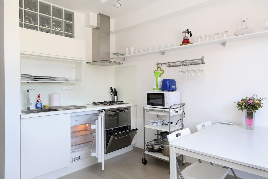 Fully equipped kitchen with dishwasher, oven, microwave, water kettle and toaster.