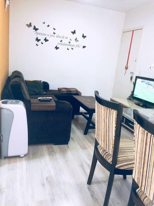 Sala de estar com TV, circulador de ar e aconchegante sofá.
