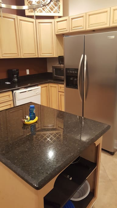 Kitchen complete with fridge, gas stove & oven, dishwasher, microwave, toaster oven, and coffee machine.