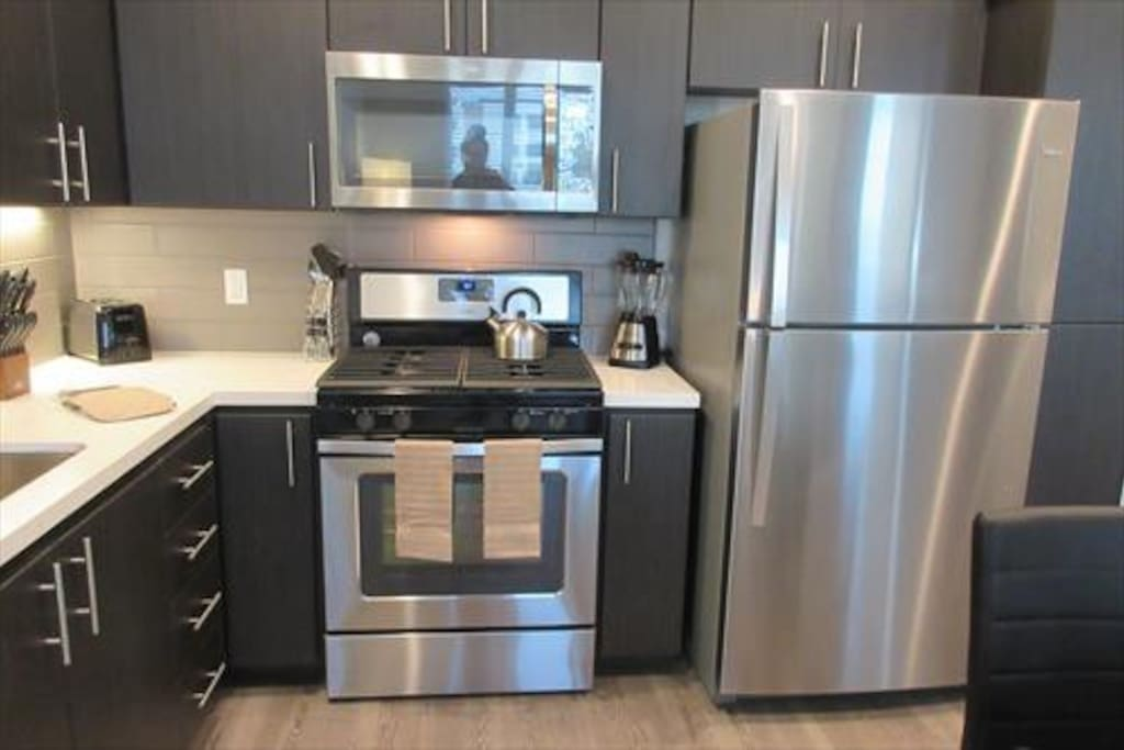 Fully equipped kitchen with full size appliances, pots, pans, and dishes.