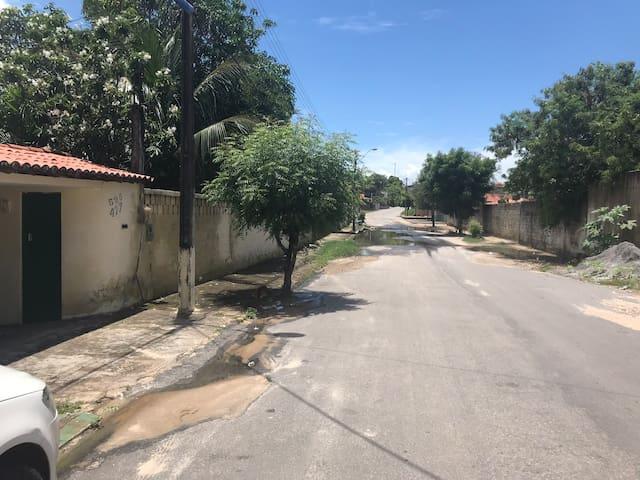 Entrada da residência, situada a algumas centenas de metros da Praia, em rua principal e de vizinhança segura. Ao fundo possível vislumbrar Posto de Saúde.