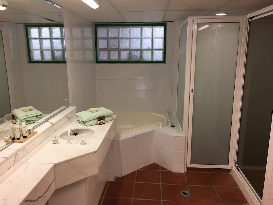 Bathroom with toilet, shower, bath, basin and hanging robe, as well as towels and toiletries