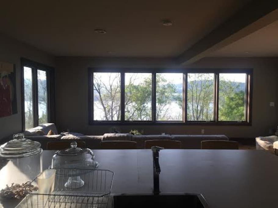 Open floor plan living space and kitchen with wrap-around windows overlooking Hudson River