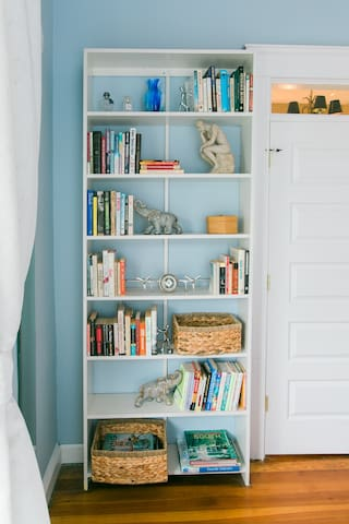 Master bedroom bookcase has a variety of books for browsing and relaxing escape.