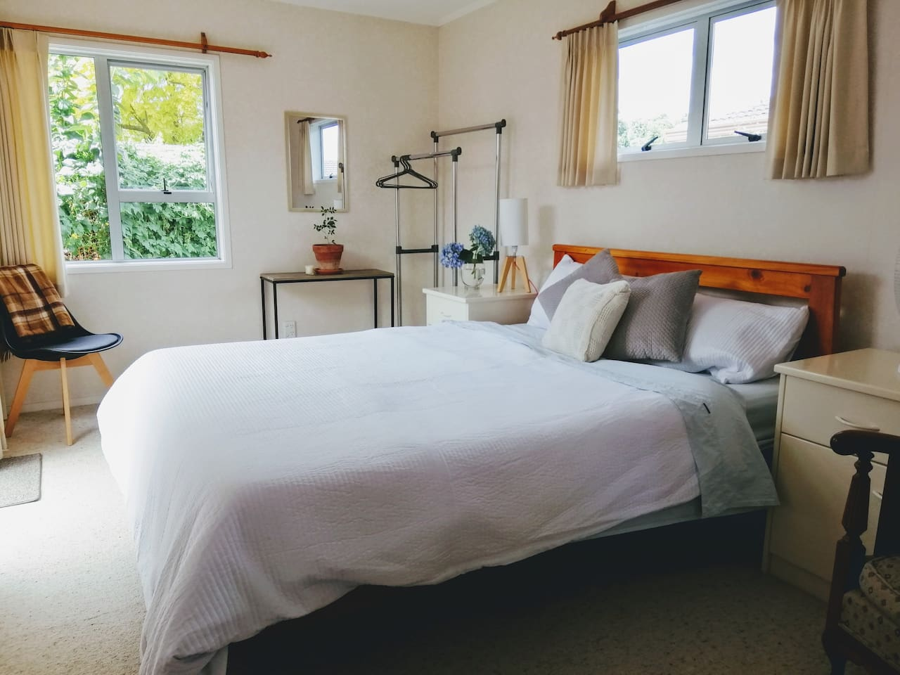 Spacious queen bed in a pleasant sunlit room with a freestanding wardrobe