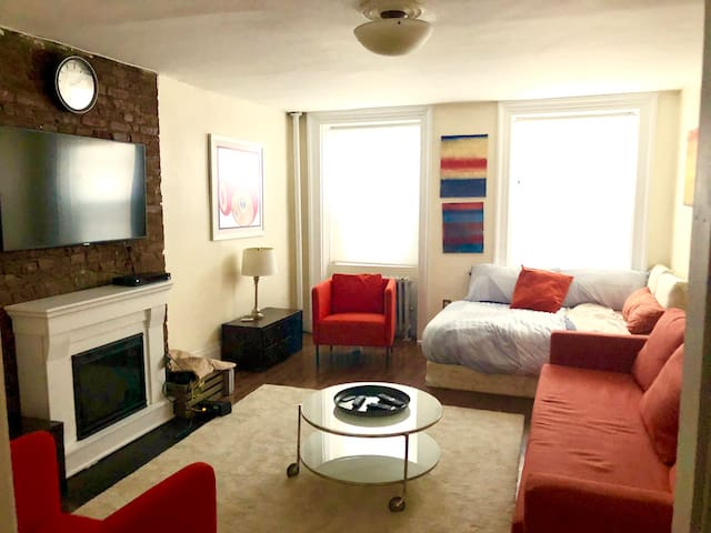 """Living room with 50"""" TV and double bed."""