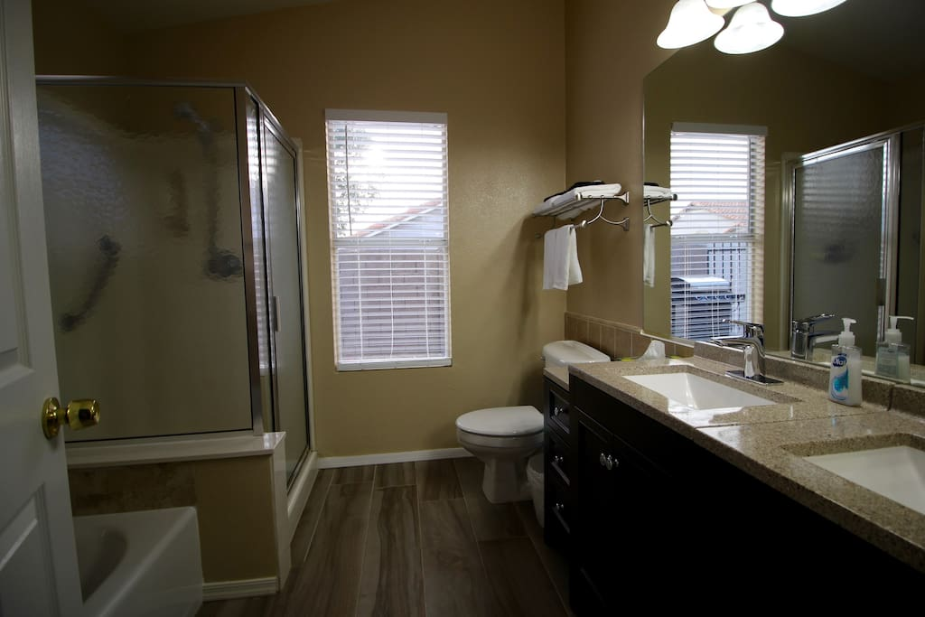 Private bathroom includes two sinks, a shower, and a bathtub.