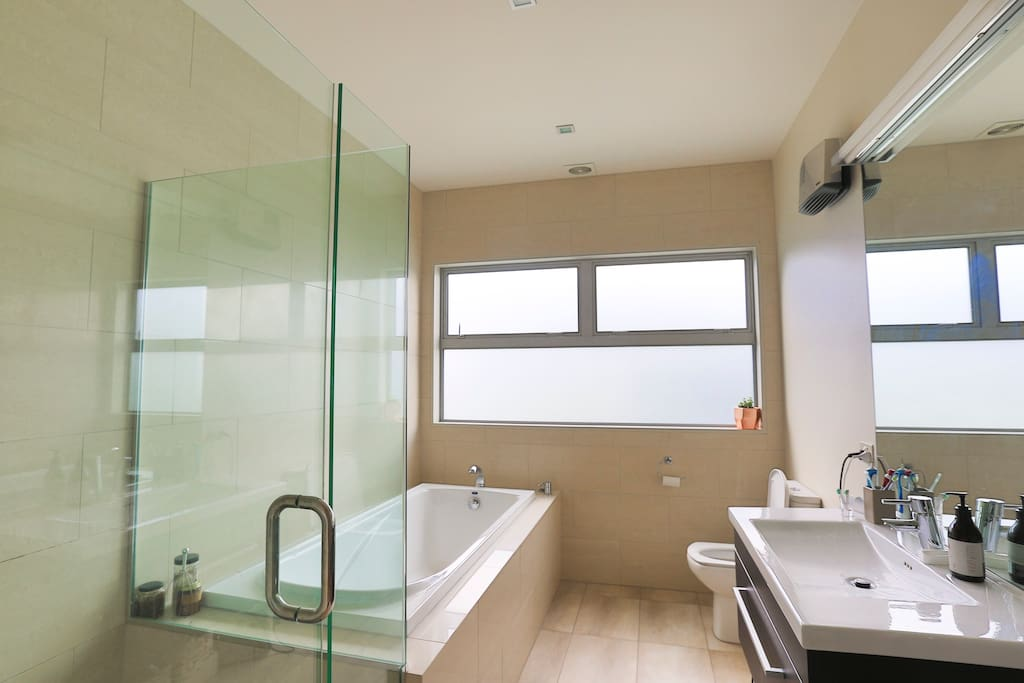Modern bathroom with glazed shower and deep bath