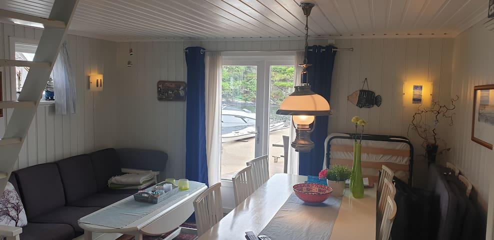 Sofa og spisebord, sydvendt med utgang til terrassen.
