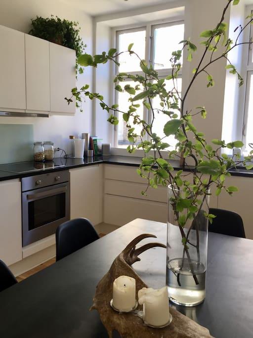 Lyst og hyggeligt køkken med spisebord