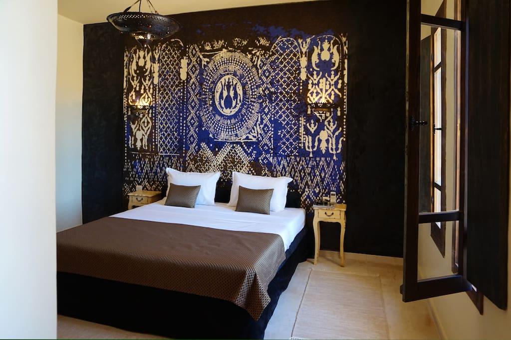 La chambre Etoile du Sud. Cette chambre bronze et bleu mystique, dispose d'unt lit King Size, d'un dressing, d'une coiffeuse, de la climatisation réversible, d'une banquette et d'une grande salle de bain privative. Accès immédiat depuis cette chambre au patio et à la piscine.