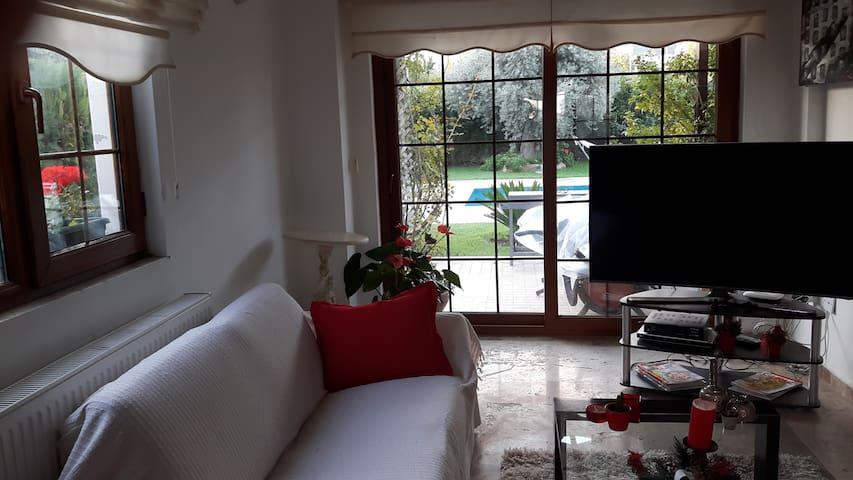 Full height windows provide views over the pool, garden &Kyrenia Mountains.
