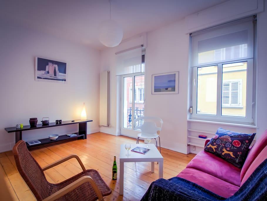 Salon spacieux avec balcon donnant sur une rue à sens unique calme