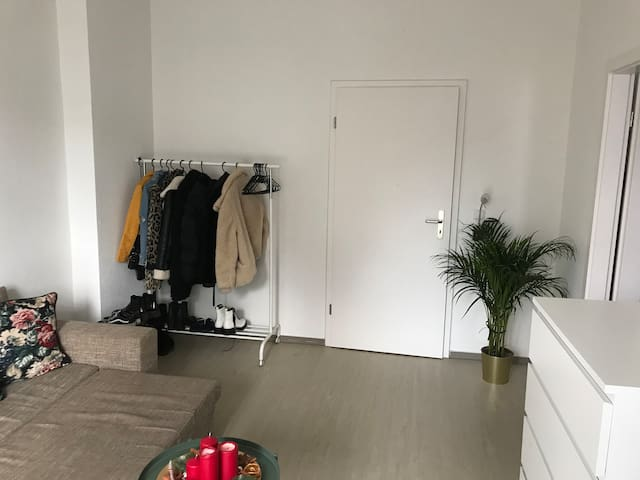 Das Wohnzimmer mit Garderobe. Die Tür führt zu dem Flur.