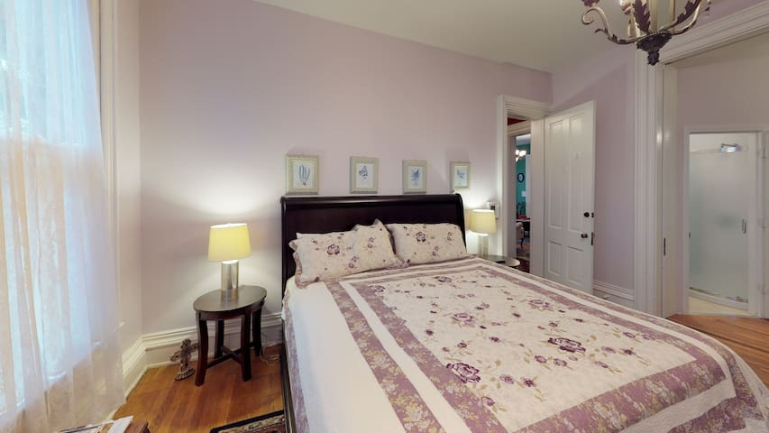 The Lilac Suite is a spacious 4 person bedroom (1 King, 1 Full/Queen) located on the main floor. Room comes equipped with an electric fireplace, flat screen TV, and an ensuite bathroom. Enjoy the new outdoor hot tub with your guests!