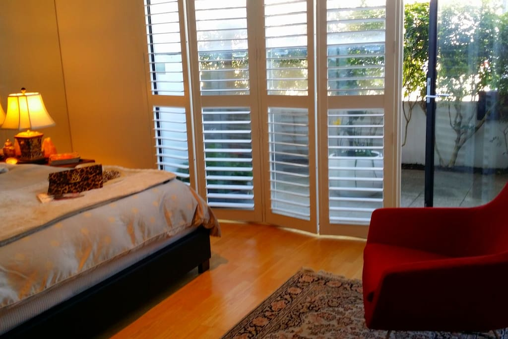 Beautiful shutters onto garden patio with vibrant Italian lounging chairs & workstation