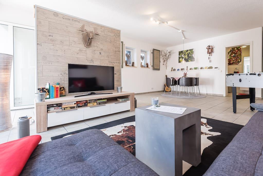 Wohnzimmer mit TV und einer großen Auswahl an Büchern. Blick auf die Essecke.