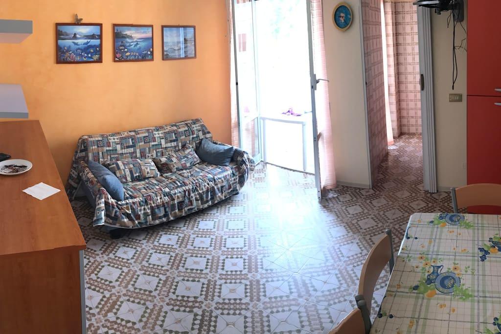 Ingresso della casa: salone/sala da pranzo. Sulla sinistra c'è un divano letto a due piazze.