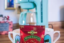 Door County Coffee & a variety of teas await your arrival! Sit and sip awhile with our lens mugs, mason jars, or currently featured holiday collection!