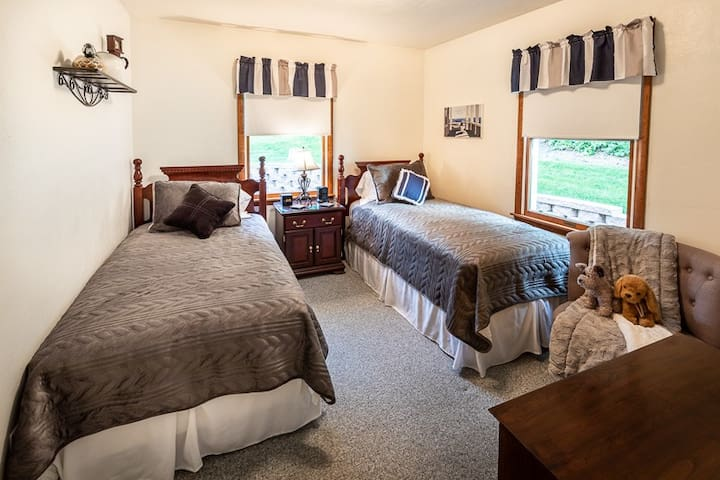 The smaller bedroom is equipped with two plush twin beds, an alarm clock, and a phone charging station.