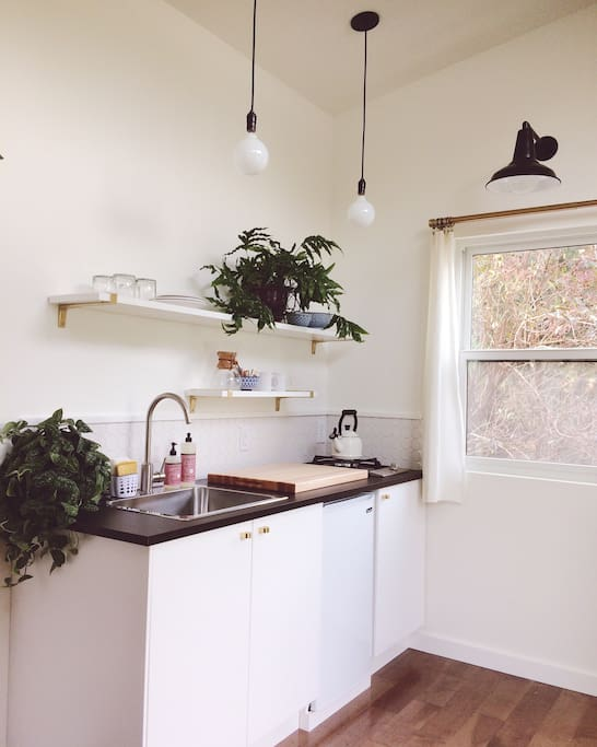 The kitchen has a mini fridge and a one burner gas stove. Out the window is a large Elderberry bush that is often filled with little yellow finches and hummingbirds.