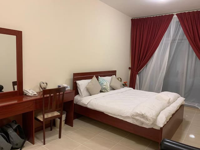 Bedroom with King size bed, sofa seating , dressing table with workspace