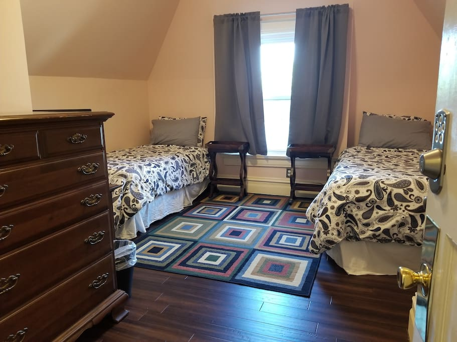 Double Twin room featuring two twin beds, dresser, keyless entry deadbolt lock on door, closet, and TV with Amazon Fire and all the best streaming services!