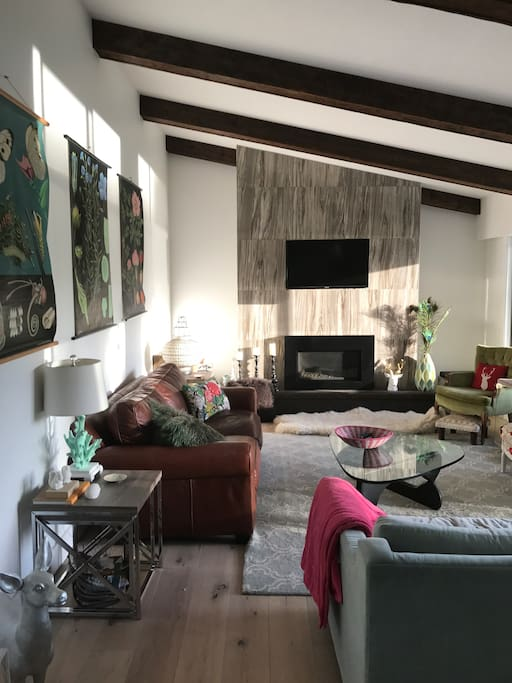 Sunny open concept living room with gas fireplace (wood stove in rec room downstairs)