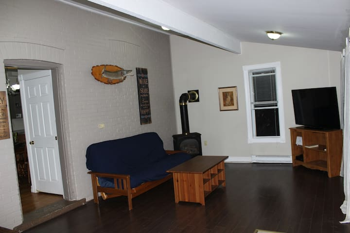 living room with fireplace and pull out futon , ac installed in window after this picture.