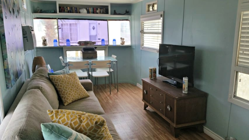 """Interior of Spartan. 40"""" TV, comfy couch, small dining table. Wifi provided."""