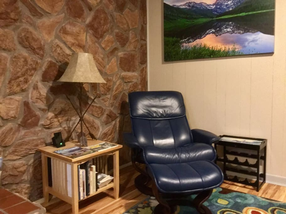 Reading area with a Stressless recliner, a charger for 3 phones, wine rack, tray, and vintage Western lamp