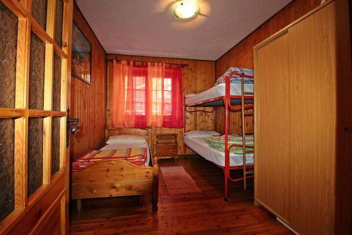 Terza camera da letto con letto a castello, letto singolo, armadio due ante e ampio finestrone.