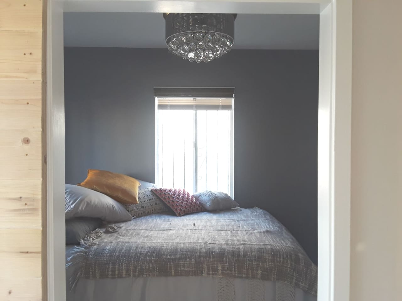 Bedroom with queen sized bed with dimmer-equipped chandelier ceiling fan