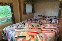 Mamas homemade quilt on our very comfortable queen bed with a private entrance to this bedroom.