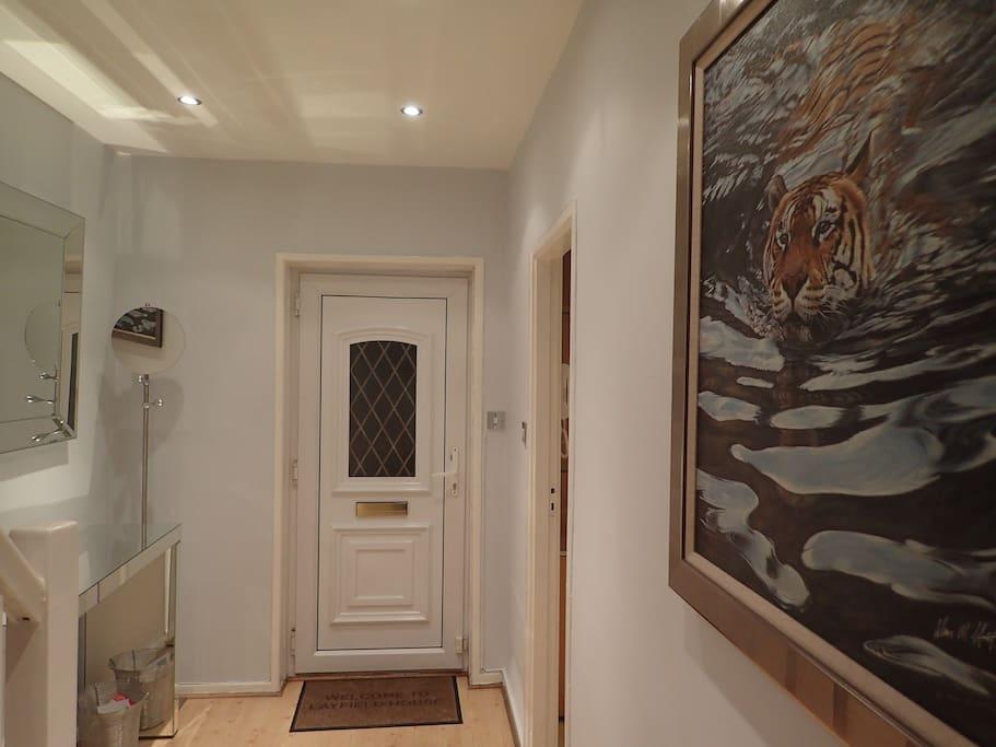 Brightly lit hallway with large vanity mirror, coat hanger & artwork