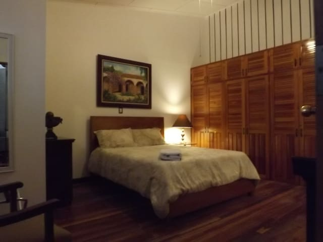 Spacious bedroom with high ceilings, roof fan