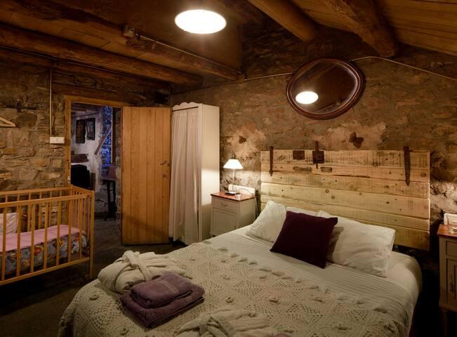 Dormitorio de arriba con estufa de leña y cuna