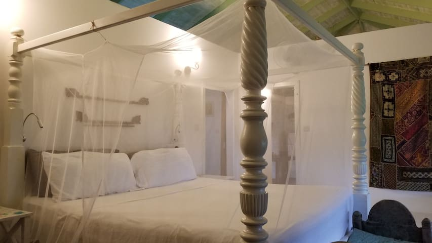 King sized 4 poster bed with superior mattress and a gel filled mattress topper, for a really restful night's sleep. Wall mounted fan, reading lights attached to either side of the bed and straight sided mosquito net.   Berbese chair and futon bed.