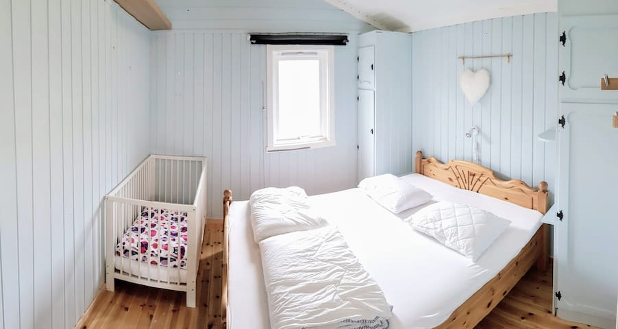 Bedroom in main building with double bed and available baby bed.