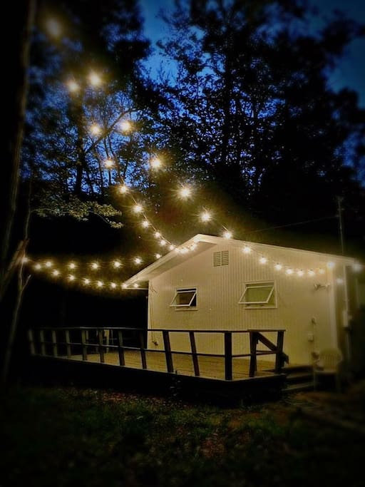 Enjoy evenings on the porch under the canopy of giant oak trees and Edison lights.