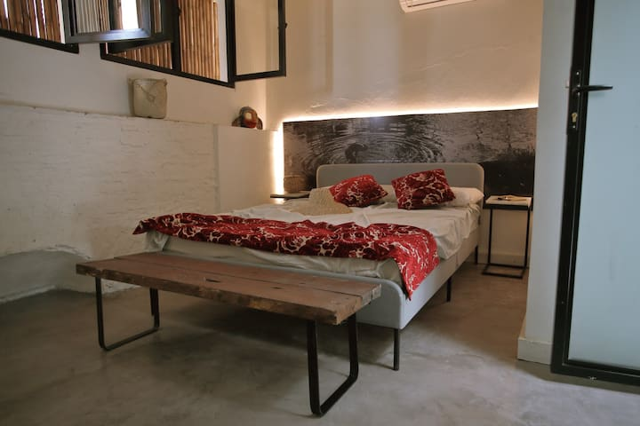 Inside the bedroom: queen bed marble tables and photo headboard.