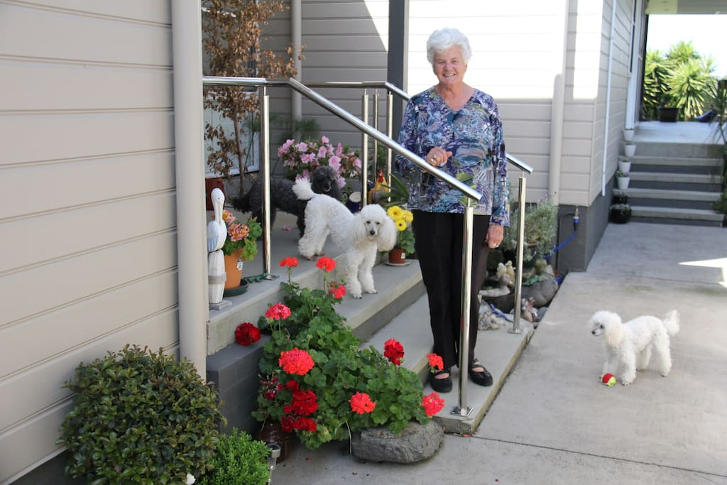 Host with two poodles at front entrance