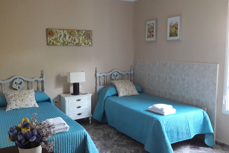 Dormitorio principal. 2 camas individuales, mesita de noche, armario y cajonera. Muy luminosa. Vistas al parque. Ventana con mosquitera.