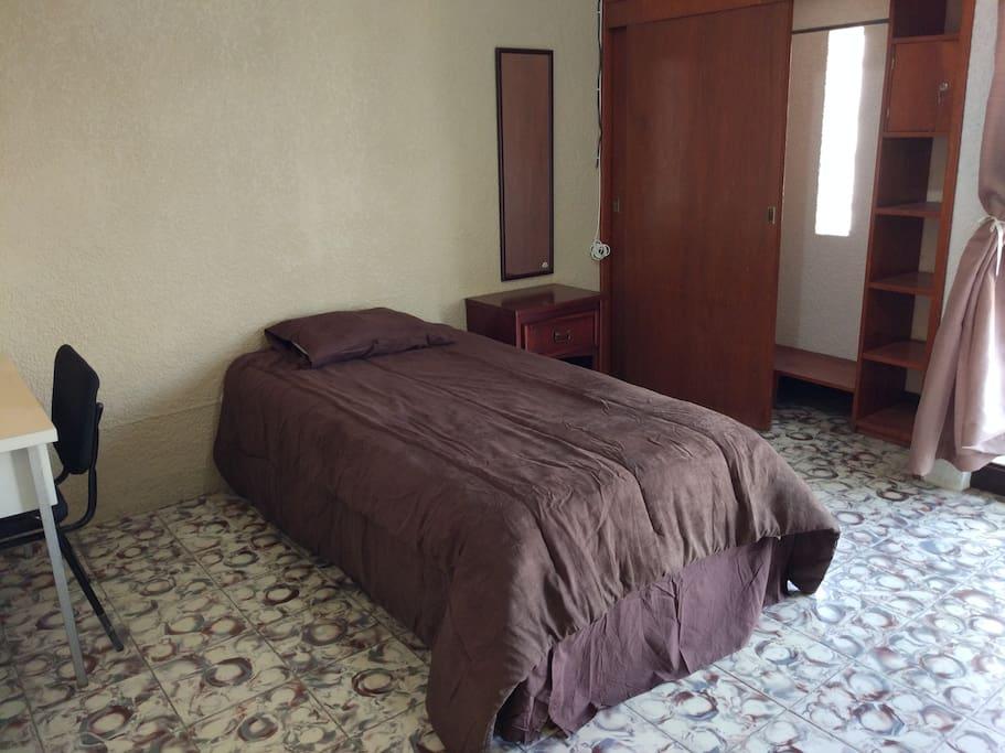 Habitación con cama individual, closet con caja de seguridad, puff de descanso, escritorio y balcon